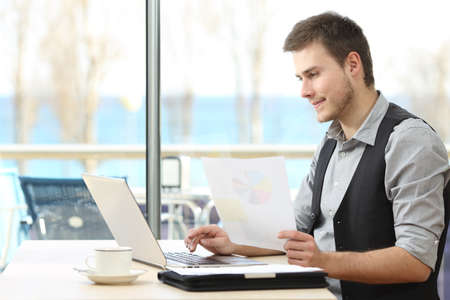 Freelance man working on line with a laptop and holding documents in a coffee shop