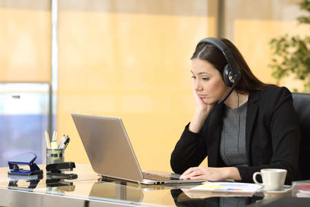 Bored operator working on line watching a laptop and listening a conversation with headset at office