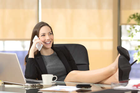 Relaxed businesswoman calling on phone sitting in a chair with the legs over the desktop at office Stock Photo