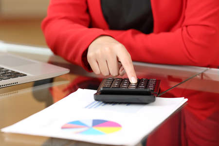 Closeup of a businesswoman hands accounting with calculator sitting in a desktop at office with her red suit in the background