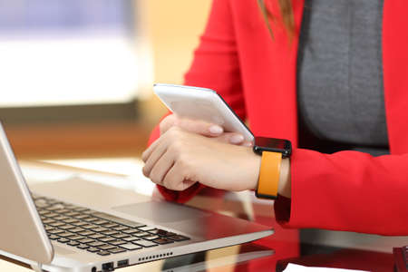 synchronizing: Entrepreneur hands synchronizing smart watch and phone sitting in a desktop at office with her red suit in the background