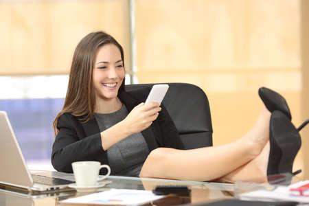 ejecutivo en oficina: Relajada mensajes de texto ejecutiva en el teléfono inteligente sentado en una silla con las piernas sobre el escritorio en la oficina