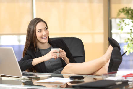 footrest: Relaxed businesswoman holding a coffee cup planning looking at side sitting on a chair with legs over the desktop at office