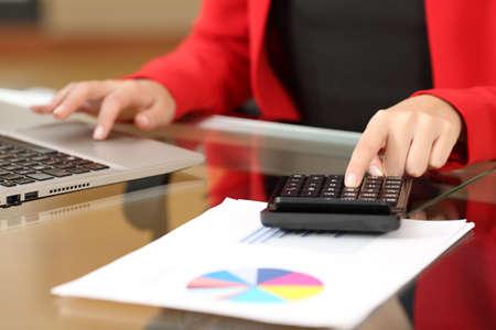 contaduria: Closeup de una mujer de negocios manos de contabilidad con una calculadora de negro y un ordenador portátil sentado en un escritorio en la oficina con su traje rojo en el fondo