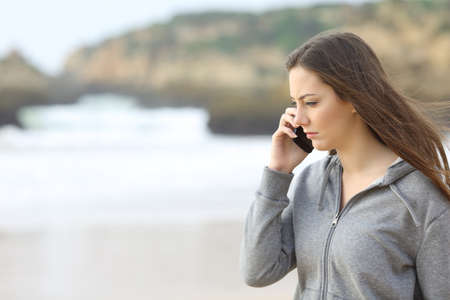 lack of confidence: Sad teen talking on the phone on the beach