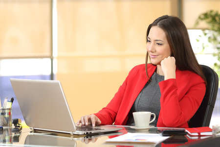 Relaxed businesswoman working watching content in a laptop sitting in a desk at office Stock Photo