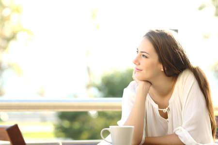 Pensieroso donna che pensa e che esamina lato seduto in un bar oa casa terrazzo