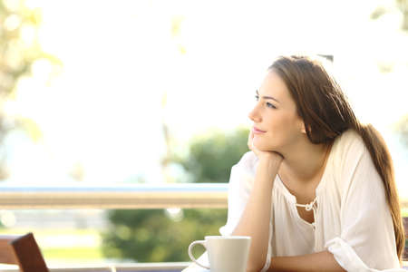 self confident: Pensive woman thinking and looking at side sitting in a bar or home terrace