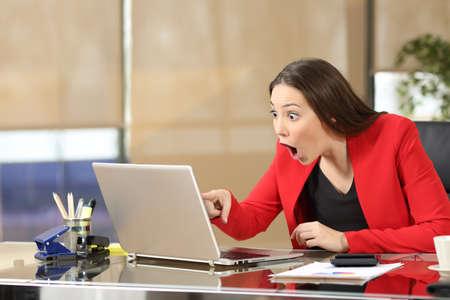 사무실에서 책상에 앉아 노트북에서 라인 놀라운 뉴스를보고 흥분된 사업가 스톡 콘텐츠