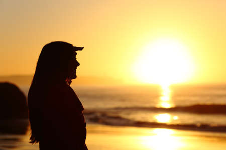 soul searching: Side view of a hopeful woman silhouette looking forward with the hand on forehead at sunset with the sun horizon and sea in the background