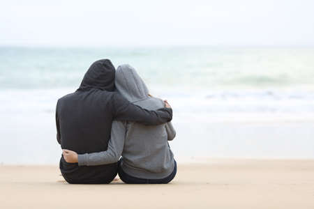 비오는 날에 해변의 모래에 앉아있는 포옹과 바다를보고 잠겨있는 청소년의 부부의 후면보기