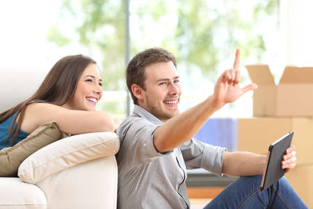 home planning: Couple planning decoration on line with a tablet and moving home in the living room