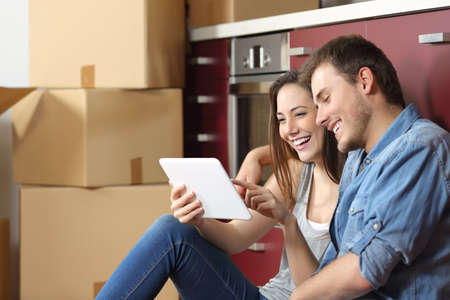 Couple moving home and buying online with a tablet sitting on the floor in the kitchen