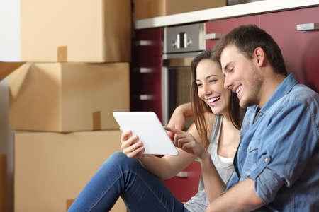 Pares que se mueven a casa y la compra en línea con una tableta que se sienta en el suelo de la cocina Foto de archivo