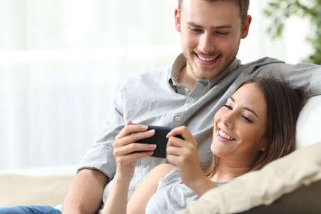 disfrutar de contenido multimedia pareja feliz en un teléfono inteligente sentado en un sofá en casa