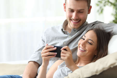Happy couple enjoying media content in a smart phone sitting on a couch at home Фото со стока