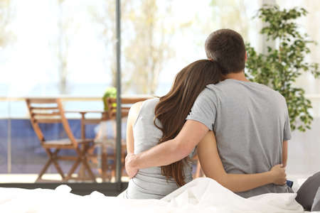 Back view portrait of a happy couple sitting on the bed looking the balcony outdoors through a window of the bedroom of a house 스톡 콘텐츠