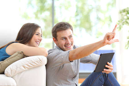 family planning: Happy couple sitting and planning new decoration with a tablet on line at home with a window in the background