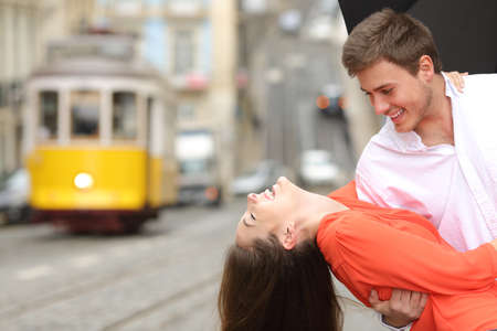 Funny casual couple flirting and joking in the street under an umbrella in a rainy day with a vintage yellow tram in the background