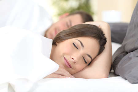 Close up portrait of a happy couple sleeping on a comfortable bed at home or hotel