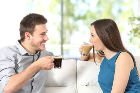 love at first sight: Side view portrait of a happy couple looking each other talking and drinking coffee sitting on a sofa at home with a window in the background Stock Photo