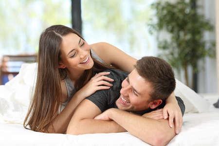 Retrato de um casal feliz ou casamento se divertindo e brincando que olham-se na cama de um quarto de hotel ou em casa Imagens