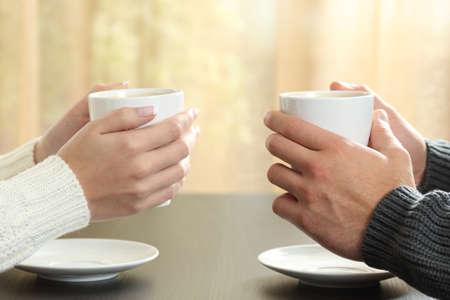 Perfil de manos de una pareja que sostiene las tazas de café sobre una mesa en invierno en un apartamento con una ventana en el fondo