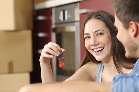 Happy new flat couple of owners showing keys sitting in the floor of the kitchen while moving home