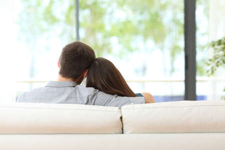 Rear view of a couple hugging sitting on a couch and looking outdoors the green background through the window of the livingroom