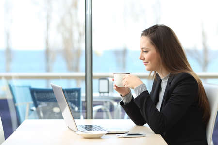 woman business suit: Businesswoman working on line with a laptop and holding a cup in a coffee shop with a window and outdoors in the background