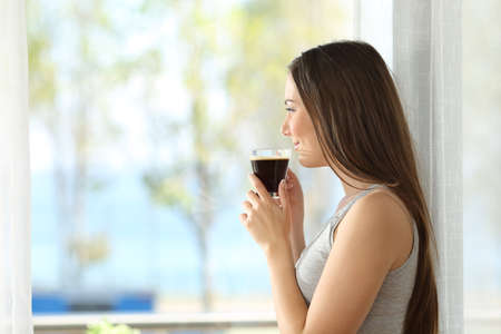 Side view portrait of a pensive girl drinking coffee and looking outdoors through a window of an hotel room or home with the sea in the background