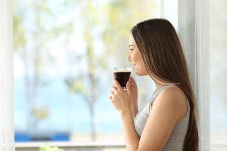 mujer mirando el horizonte: Vista lateral retrato de una niña pensativa beber café y mirando al aire libre a través de una ventana de una habitación de hotel o casa con el mar de fondo Foto de archivo