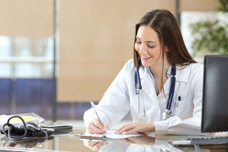 health professional: Doctor woman working writing in a medical history sitting in a desktop at consultation