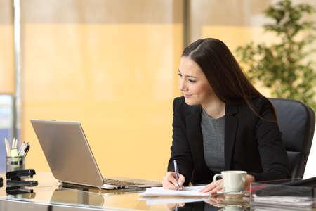オンライン作業、オフィスでデスクトップに座ってメモを取って幸せな集中の実業家