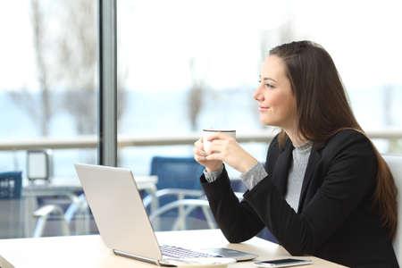 Portret van een peinzende zakenvrouw dragen pak denken en plannen op zoek buiten door het raam in een bar met de horizon op de achtergrond