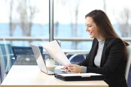 Retrato de una bella empresaria de trabajo en línea con un ordenador portátil y la celebración de los documentos en una cafetería con una ventana en el fondo