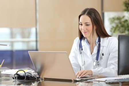 Doctor concentrado que trabaja en línea con un ordenador portátil sentado en un escritorio en una consulta Foto de archivo - 64947172