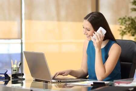 Entrepreneur working on line with a laptop and talking on phone sitting in a desk at office