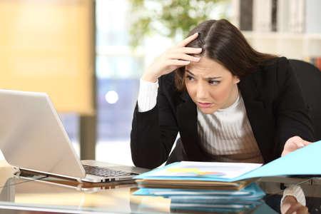 Ongerust gemaakte onderneemster met een moeilijke baan die op haar laptop online in een bureau op kantoor letten