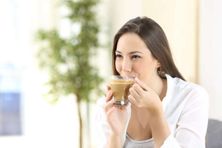 Woman sipping and drinking a delicious coffee with milk looking away at home