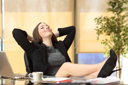 Satisfied relaxed businesswoman sitting in a chair with legs over the table and hands in the head enjoying her new job at office Stock Photo