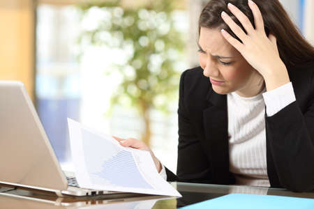 Worried businesswoman in bankruptcy watching decreased sales statistics in a paper document at office