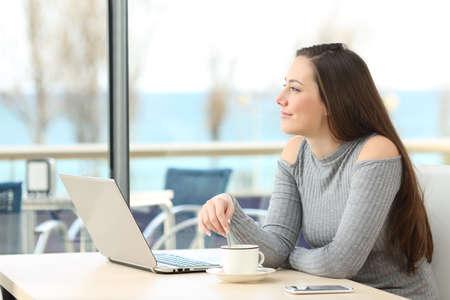 Mulher pensativa feliz pensando e planejando olhar o horizonte ao ar livre através de uma janela em um bar com o mar ao fundo