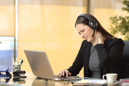 Stressed businesswoman suffering neck ache while is working on line sitting in a desktop at office