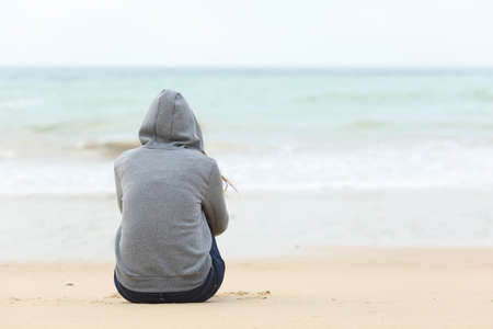 self esteem: Back view of one teenager girl thinking alone and watching the sea sitting on the sand of the beach with the horizon in the background