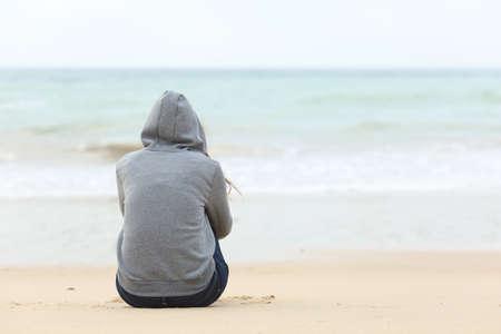 mujer pensativa: Vista posterior de la niña de un adolescente pensando solo y mirando el mar sentado en la arena de la playa con el horizonte en el fondo