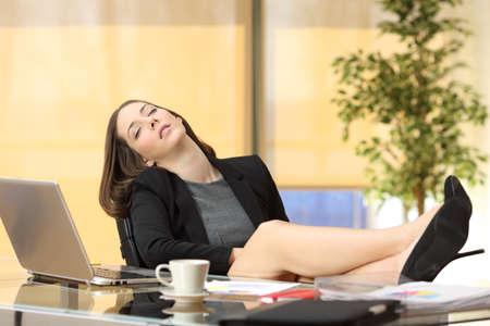 Lui of moe zakenvrouw slapen op het werk met de benen over de tafel op kantoor Stockfoto