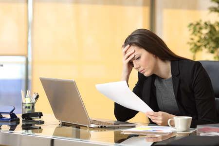 Bezorgd zakenvrouw het lezen van een bericht tijdens werkt zittend in een bureau op het kantoor Stockfoto
