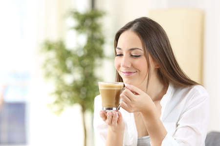Happy woman enjoying of coffee with milk watching the cup at home