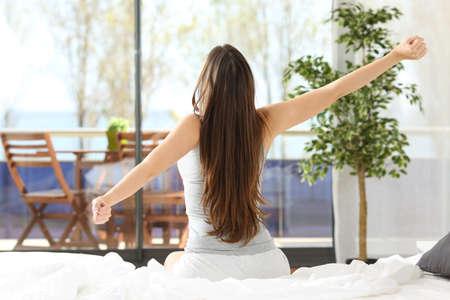 aire puro: Mujer que estira los brazos y despertar sentada en la cama en un hotel o en casa habitación mirando al mar al aire libre a través de la ventana Foto de archivo